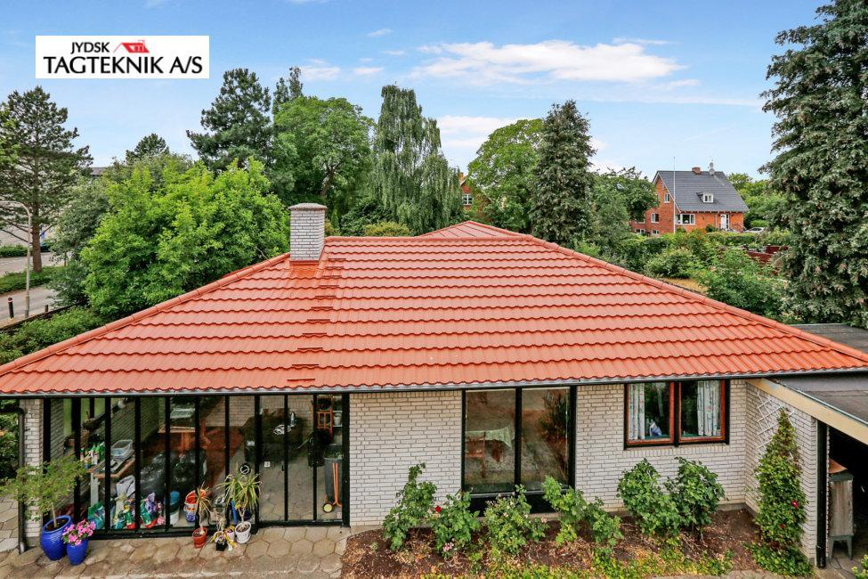 Grå murstensvilla med rødt tag